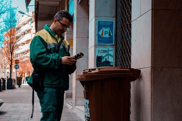 Un operari davant d'un contenidor de matèria orgànica a un comerç del carrer Montcada - ARXIU