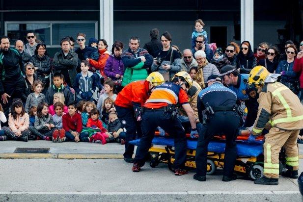 Bombers voluntaris, policia local i personal sanitari traslladen el ferit a l'ambulància, en el simulacre d'accident
