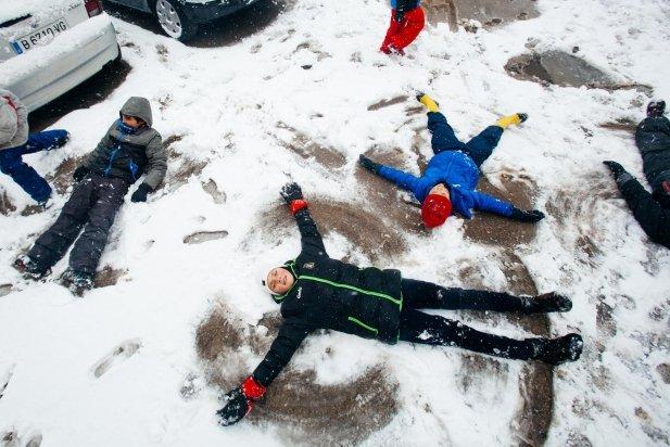 Nens i nenes juguem amb la neu al costat de l'esglèsia de Sant Esteve