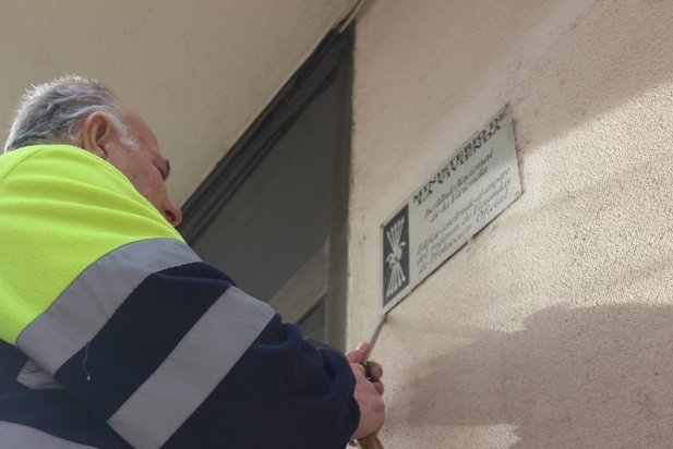 Un membre de la brigada retirant el 2017 una placa de l'antic Instituto Nacional de la Vivienda