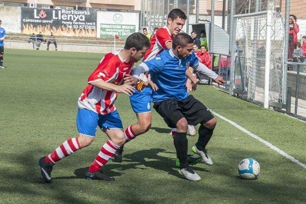 Dani Quesada lluita una pilota davant l'oposició de dos rivals