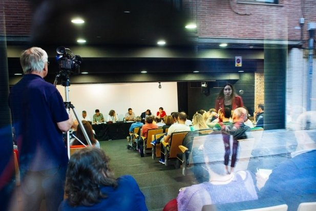 Una noia mira el debat de candidats a la sala d'actes d'El Mirador