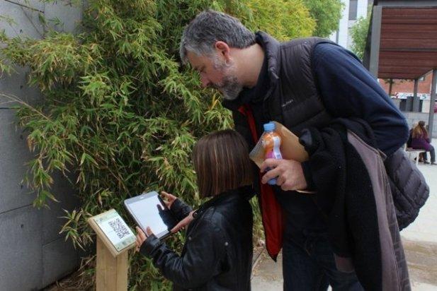 Oriol Vicente, de l'Arxiu d'Història, provant el codi QR de la plaça Calissó