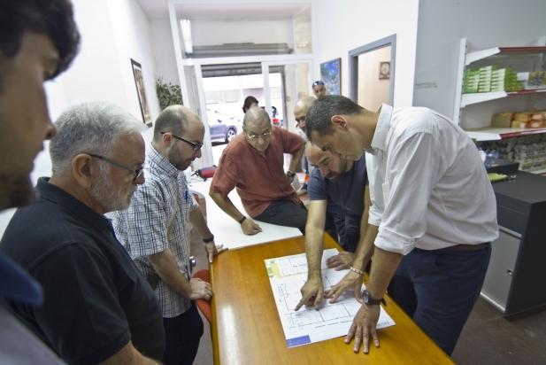 L'arquitecte tècnic de l'Ajuntament mostra els plànols de l'ampliació del local de Càritas Castellar – Via Solidària / Carles Díaz