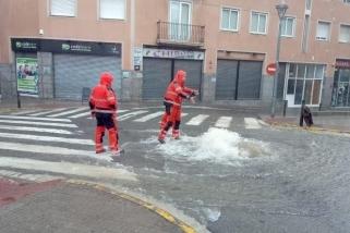 Els Bombers Voluntaris de Castellar fent tasques en una tapa d'embornal amb sobreeiximent d'aigua, a l'alçada del passeig, plaça Calissó.  || BOMBERS VOLUNTARIS DE CASTELLAR