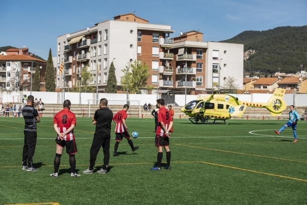 Els jugadors de la UE Castellar esperen que s'enlairi l'helicòpter per tornar a jugar.