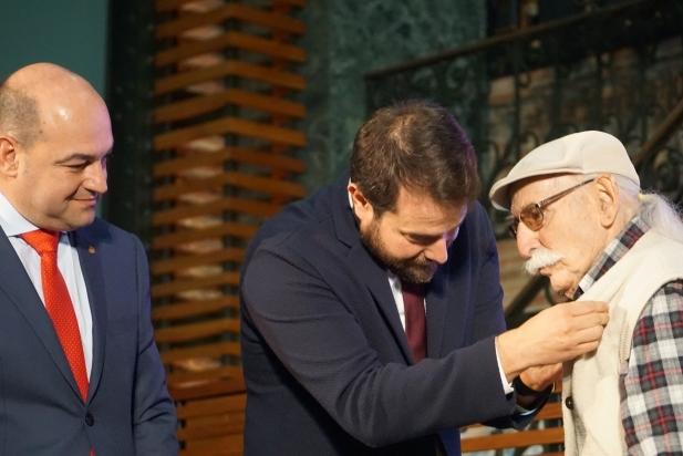 Torras rebent l'ensenya d'or de mans del Secretari general d'Esports, Gerard Figueras, i el president de la FEEC, Jordi Merino